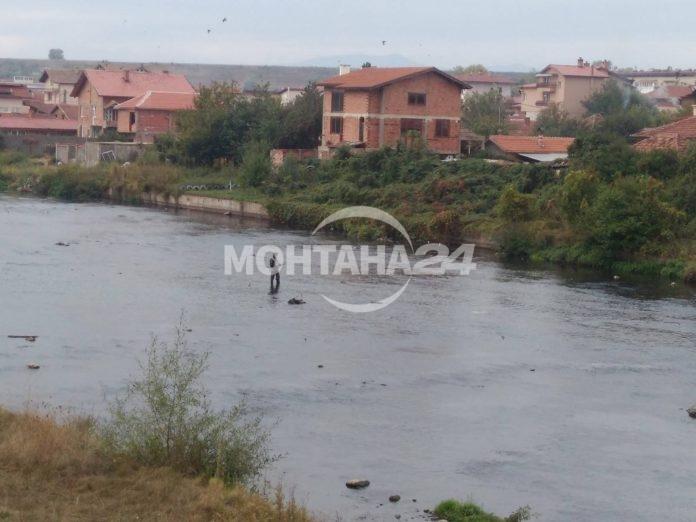 Ентусиаст рибар в студените води на река